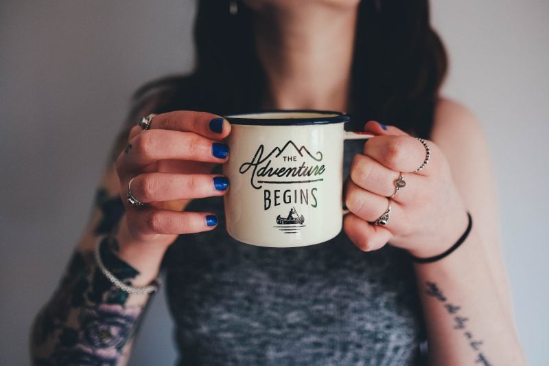 Woman holding cup that says 'The Adventure Begins'