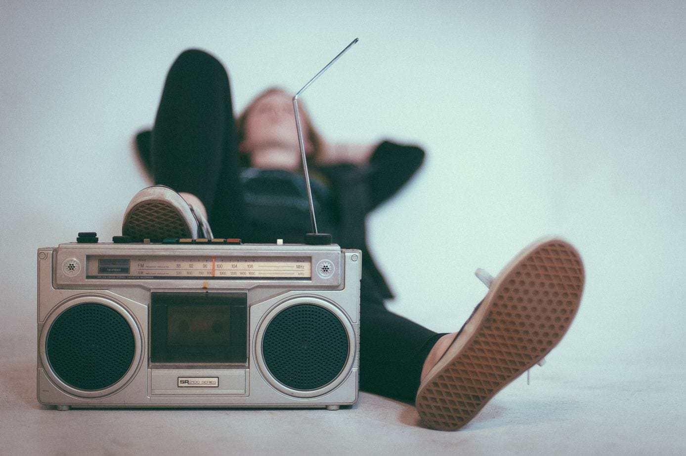 A blurry shot of a woman in sneakers reclining with her foot on a vintage sound system