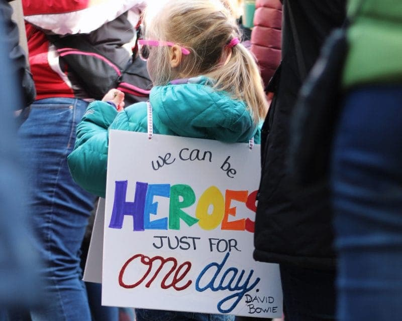 "Child wearing a sign saying ""We can be heroes by David Bowie"""