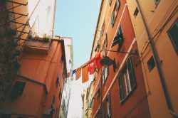 Wet clothes hanging on a line between two residential buildings in an alley in Genoa
