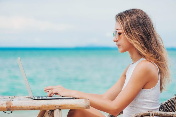 Young woman freelancer in dress sitting at the table on ocean background, using laptop on the beach.