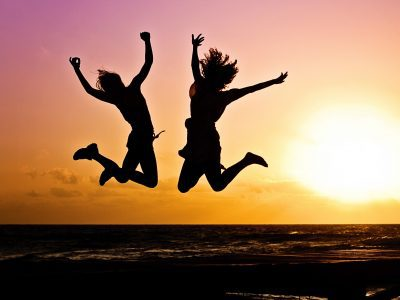 Two people jumping for joy with the sunset behind them