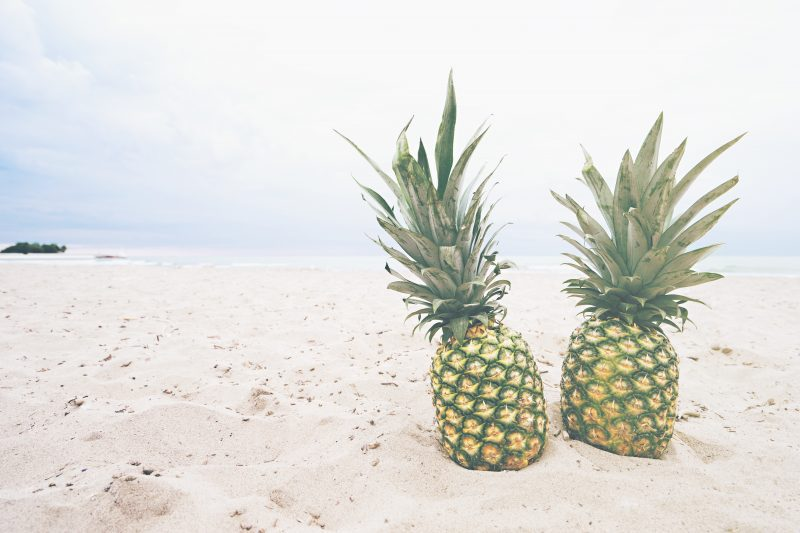 2 similar looking pineapples on a beach.