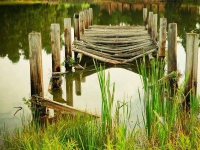Broken bridge leading out to the water making it impossible to cross the lake.