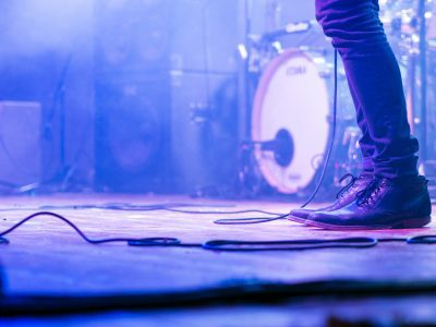 A low shot of a musician's jeans and shoes on a stage