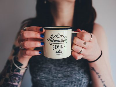 "Woman holding cup that says ""The Adventure Begins"""