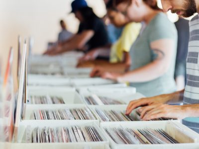 People searching through boxes of vinyl records.