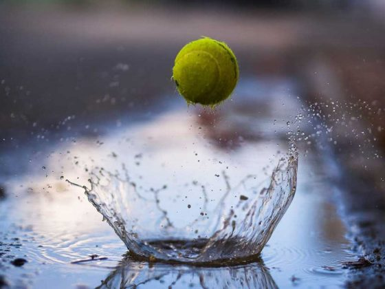 Tennis ball bouncing through a puddle of water.