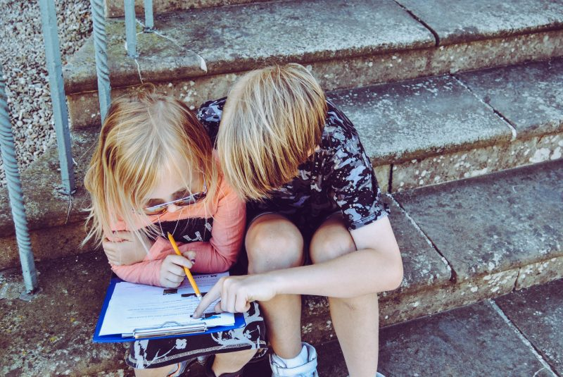 Two children writing on a piece of paper.