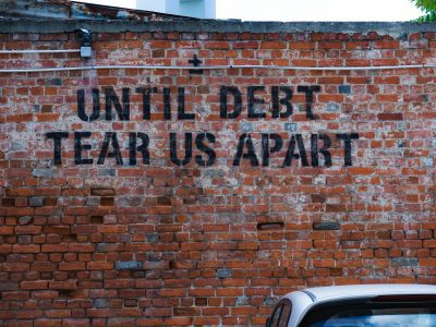 "Brick wall with ""until debt tear us apart"" painted on it."