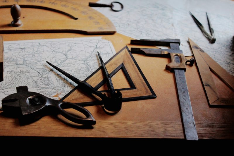 A map, protractor, and other old style measuring tools on a desk.