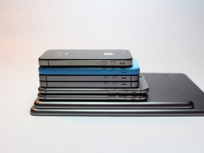 Many mobile phones and tablets stacked on one another.