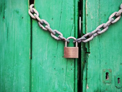 Padlock and chain locking a green door.