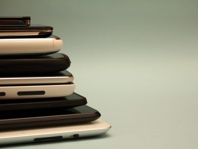 Multiple mobile phones stacked on top of one another.