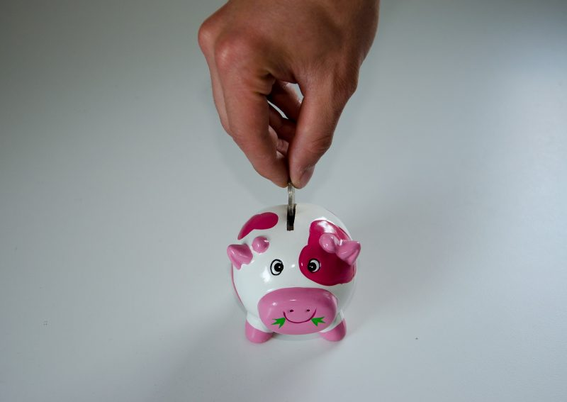 Person placing a coin in the coin slot of a piggy bank