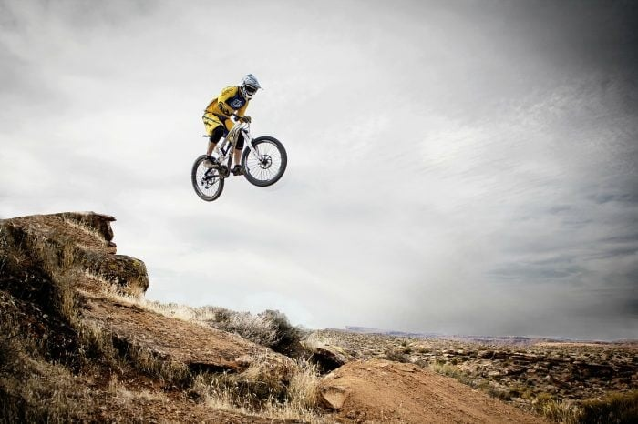 person on a mountain bike jumping off a dirt mound