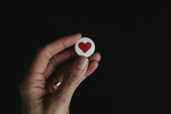 person holding a small badge that has a red heart on it