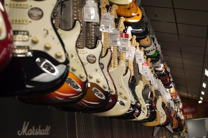row of guitars hanging in a guitar shop.