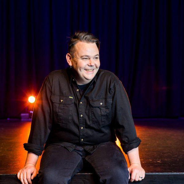 Sam Hemphill sitting on a stage