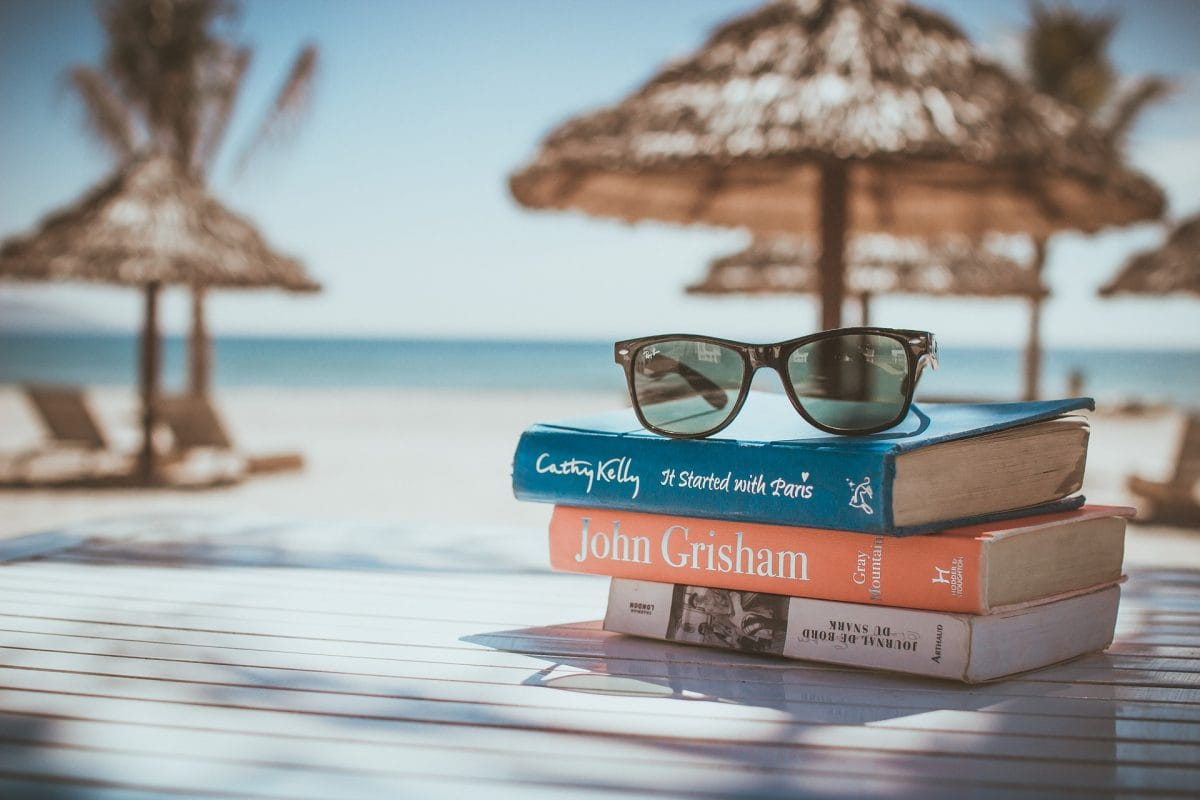 Beach setting showing three books on a table with a pair of sunglasses on top of them.